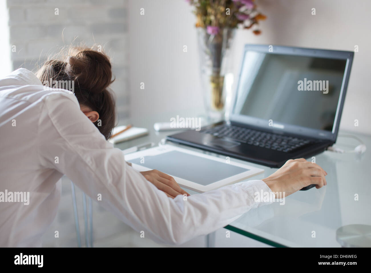 Tired woman sleeping on workplace - Stock Image