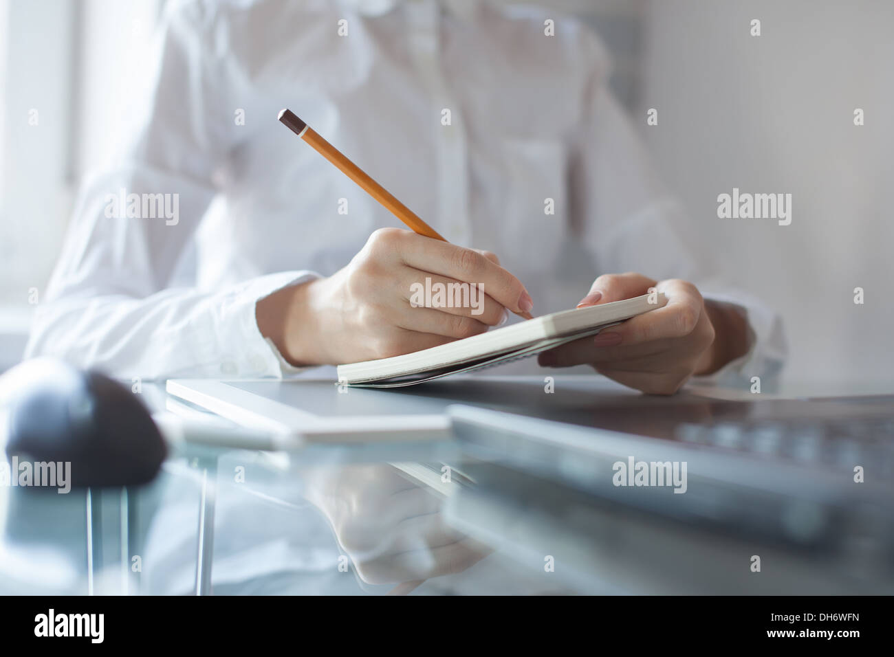 Woman's hand using a pencil noting on notepad - Stock Image