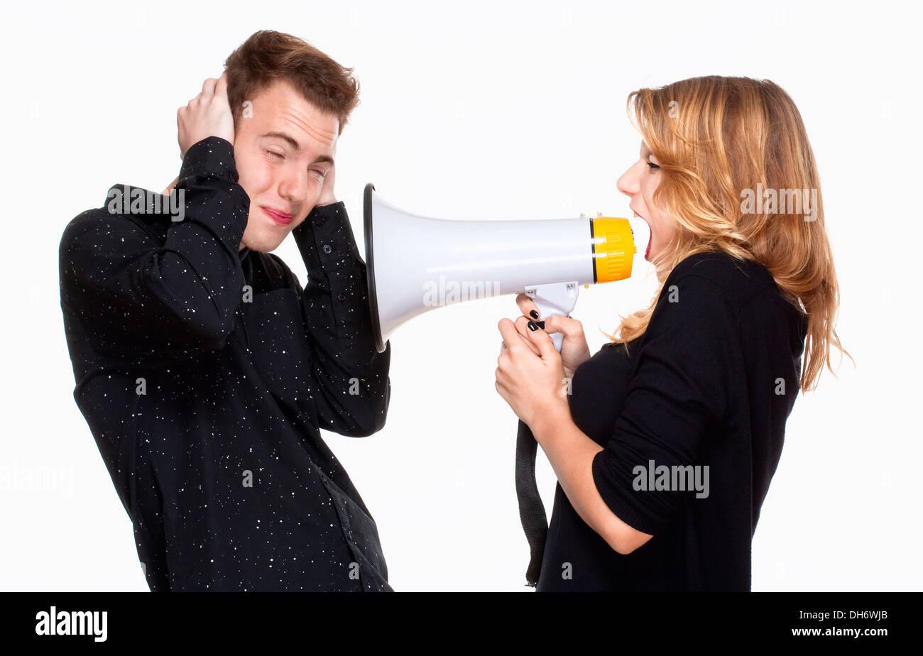 angry girlfriend screaming in megaphone, boyfriend covering his ears - Stock Image