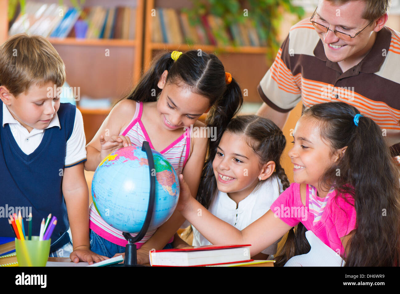 Portrait of pupils looking at globe with their teacher during geography lesson - Stock Image