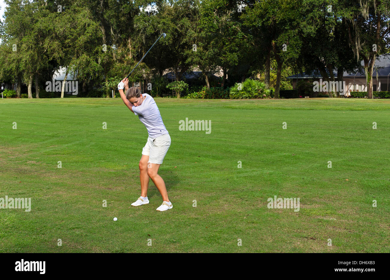 Young woman taking a shot on the fairway of a golf course at the Grenelefe Resort, Haines City, Central Florida, USA - Stock Image