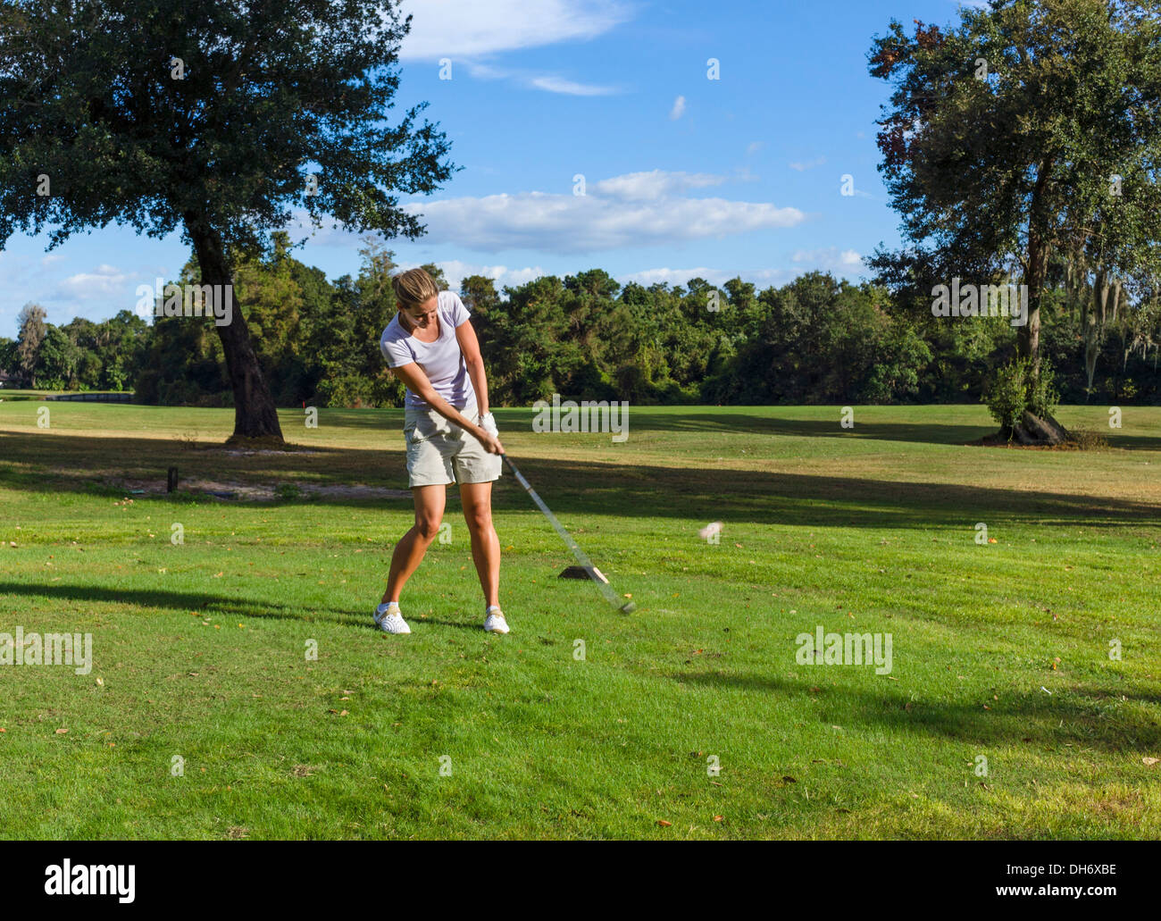 Young woman teeing off on a golf course at the Grenelefe Resort, Haines City, Central Florida, USA - Stock Image