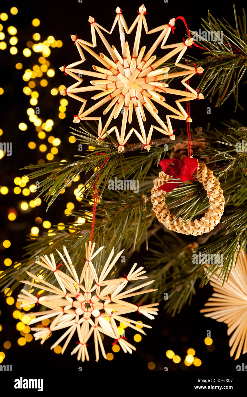 Fragile handmande straw christmas ornaments hanging in the tree Stock Photo