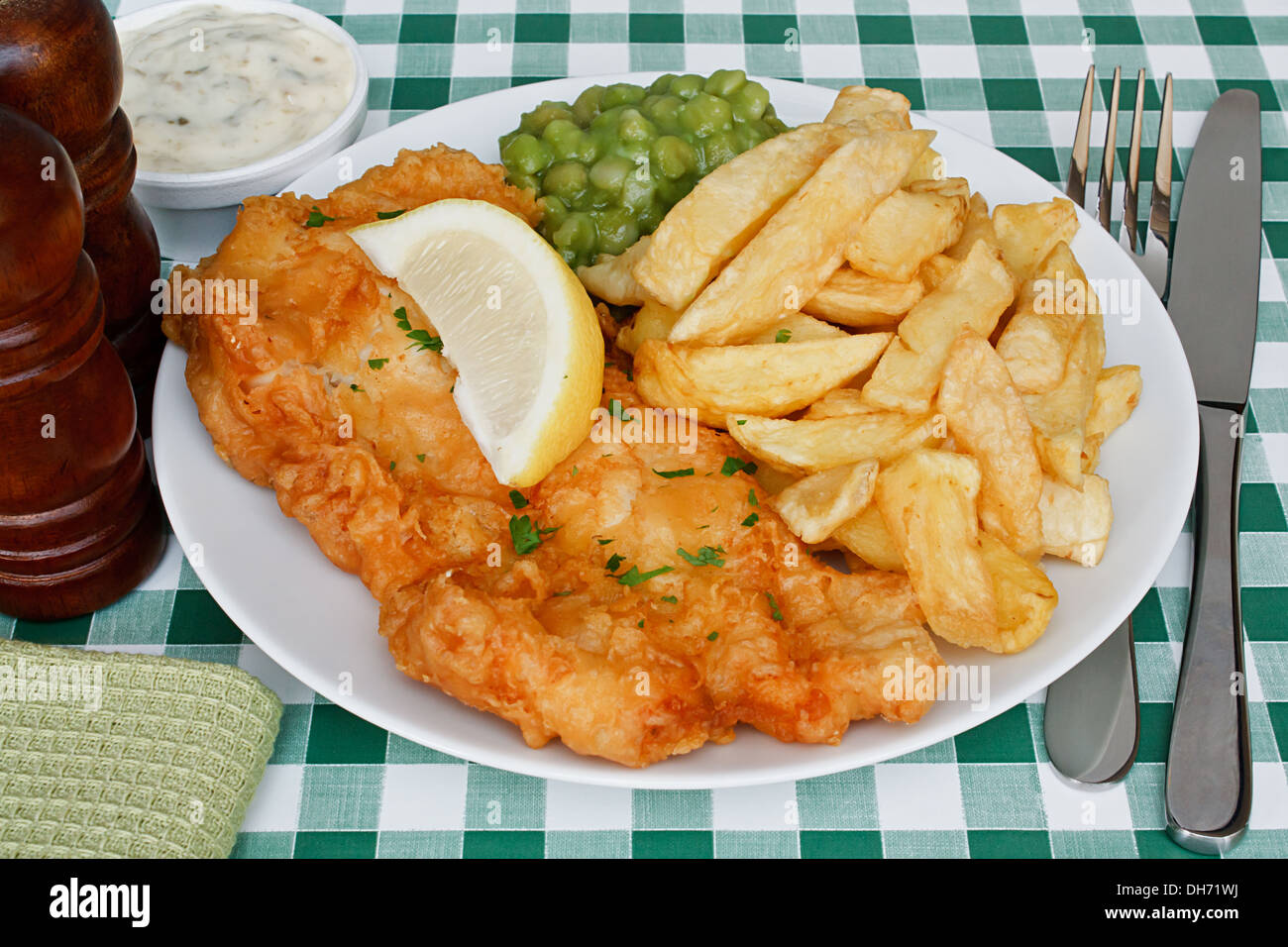Plate of fish and chips with mushy peas and a slice of lemon on a diner table. A traditional British Seaside Dish - Stock Image