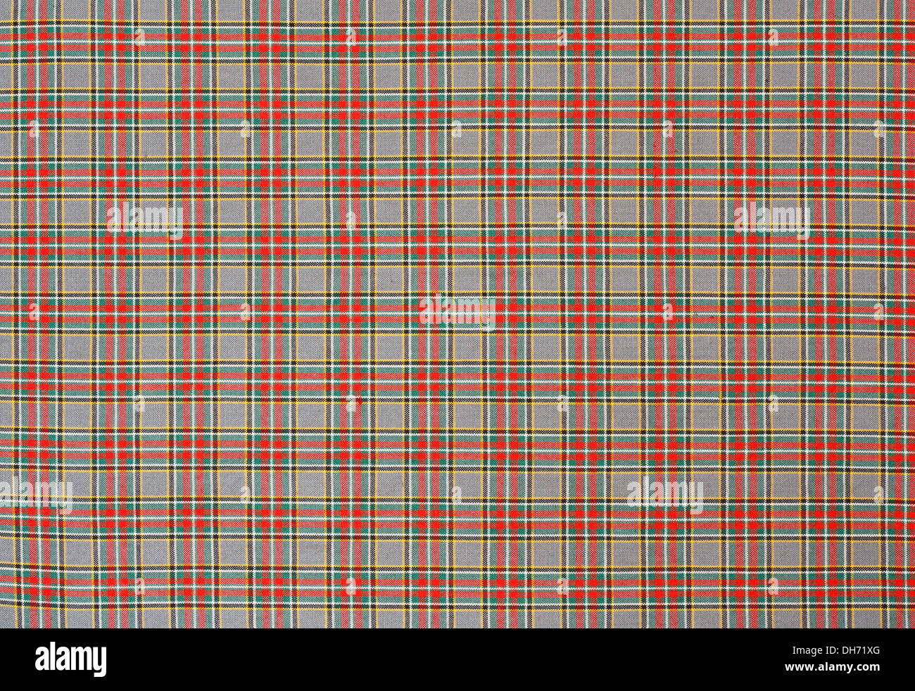 Scottish tartan background a checked plaid weave pattern with red, green and yellow colours. - Stock Image