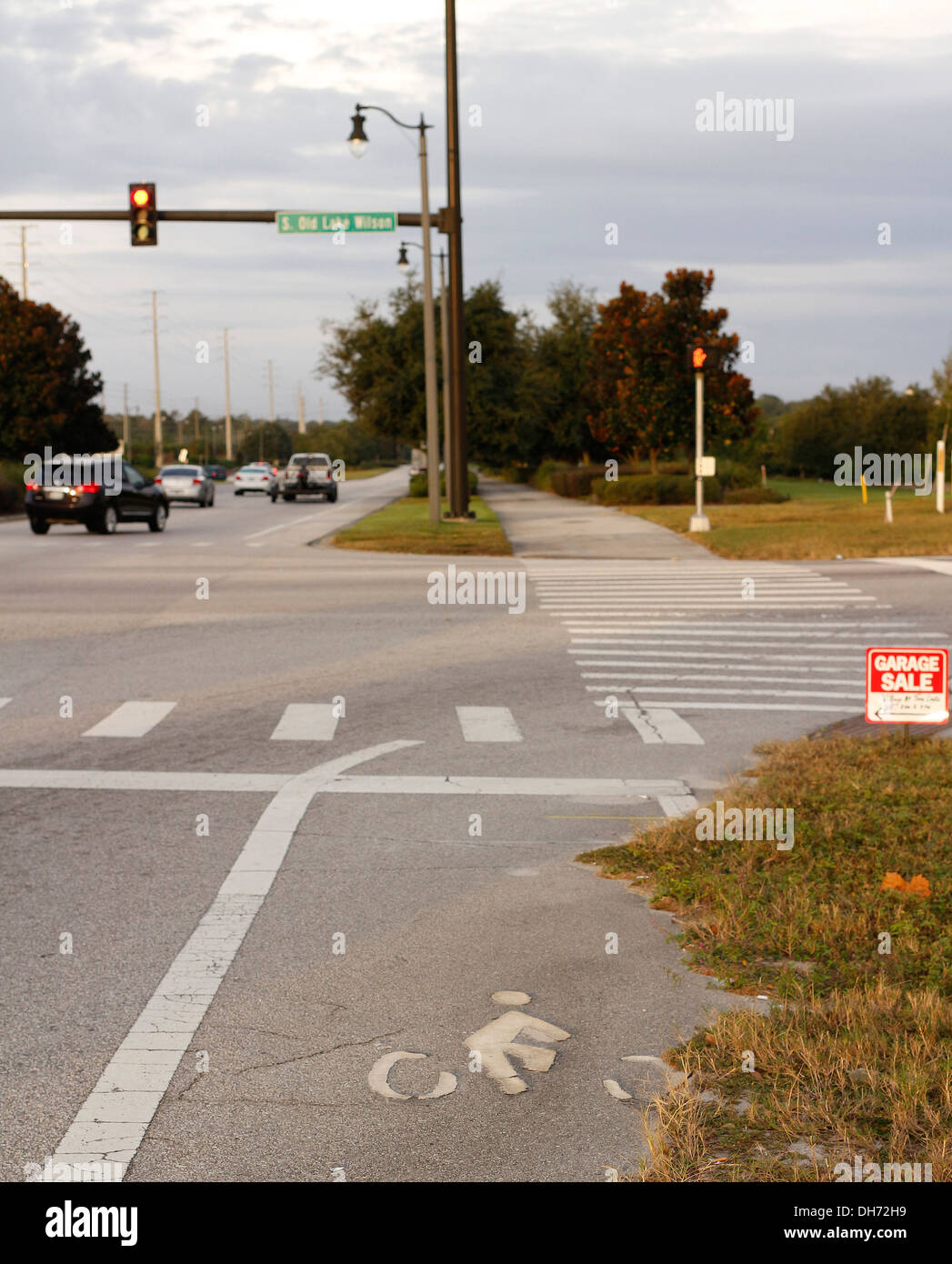 Cycle track markings on at a busy interstate high intersection, Partly worn out partly overgrown, November 2013 - Stock Image