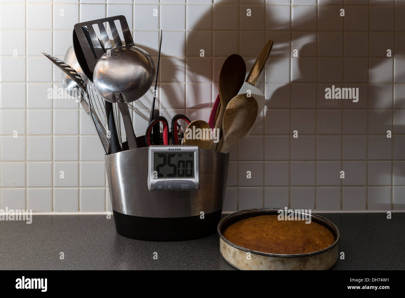 Kitchen utensils and a fresh baked cake. - Stock Image