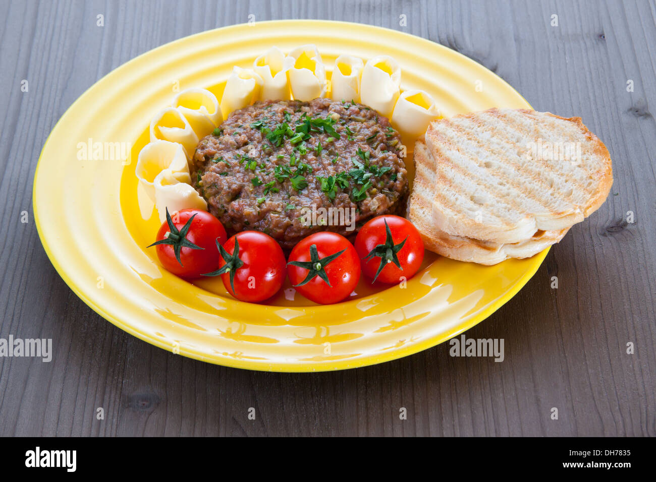 Steak tartare with toasted bread, tomatoes and butter on yellow plate Stock Photo
