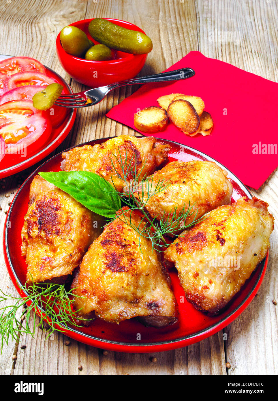 Roast chicken with tomatoes and cucumbers on a wooden background - Stock Image