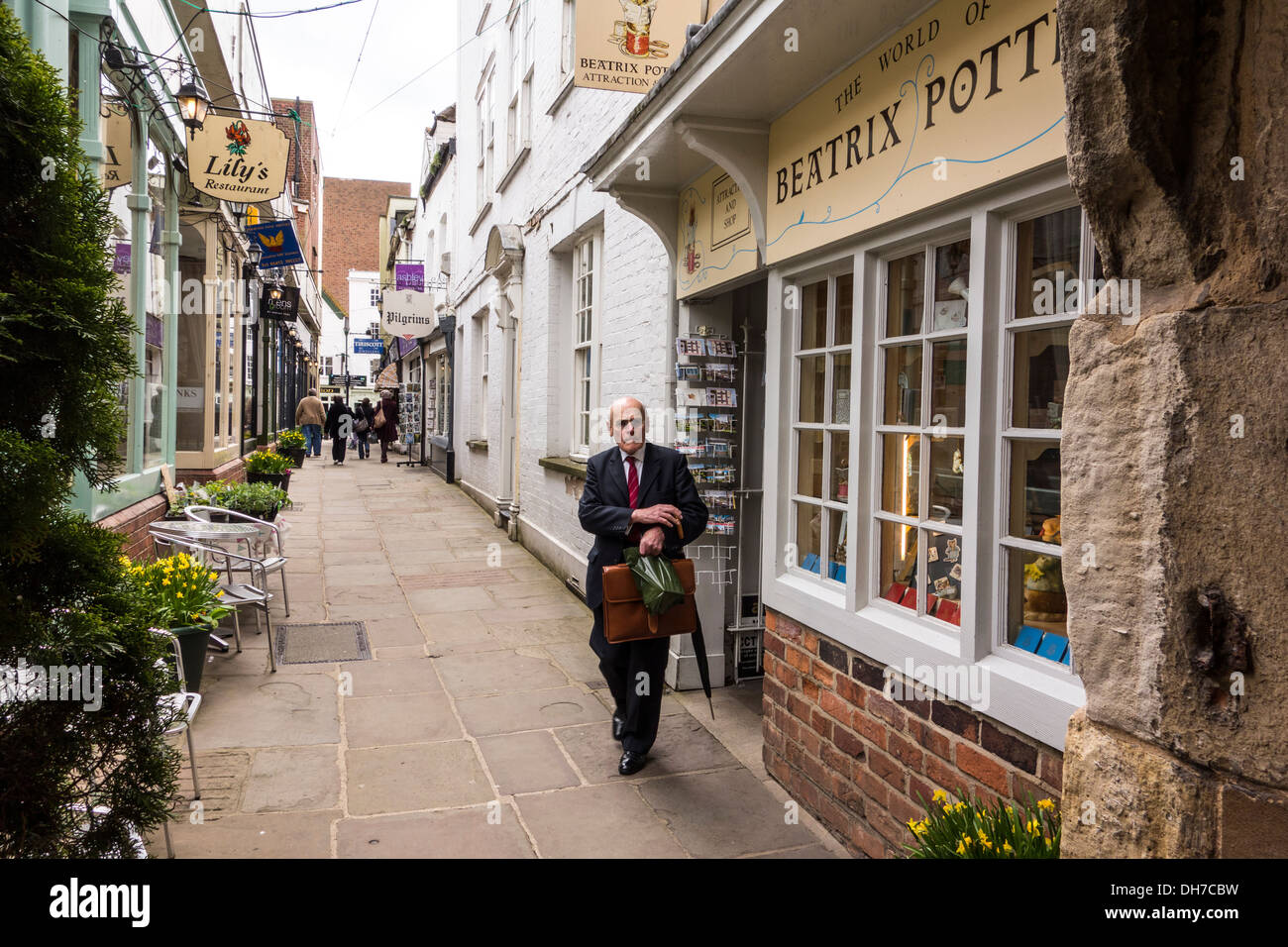 An elderly English gentleman coming out of Beatrix Potter shop in College Court, Gloucester, Gloucestershire, UK - Stock Image