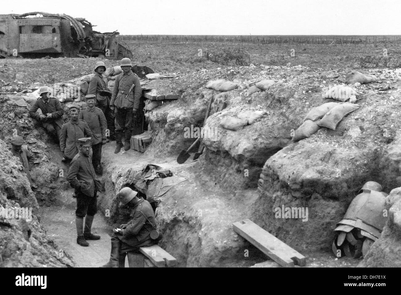 German troops rest in a frontline trench. In the background is a disabled British tank. - Stock Image