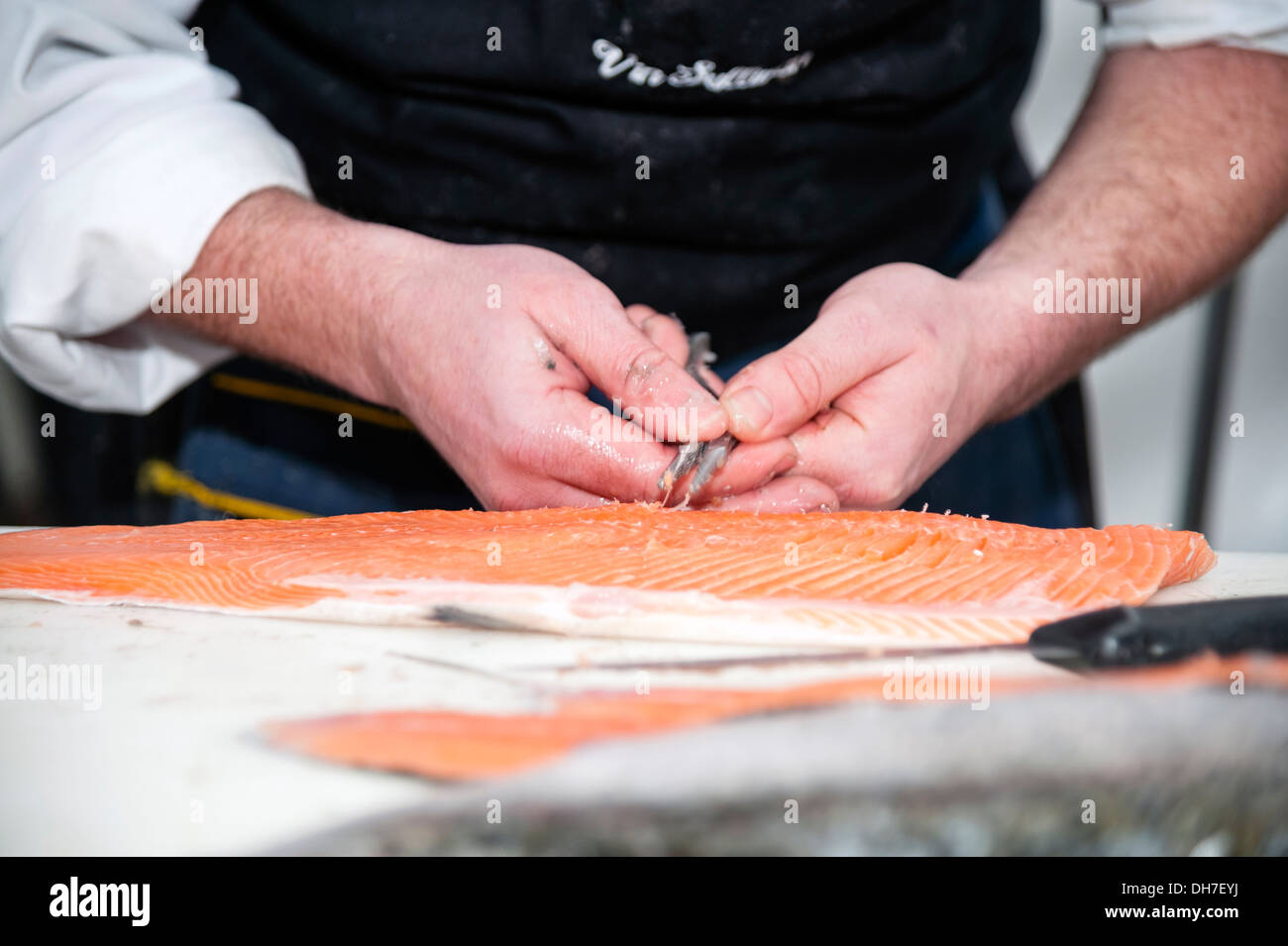 Fishmonger de-boning a salmon fillet with a pair of pliers, UK. - Stock Image
