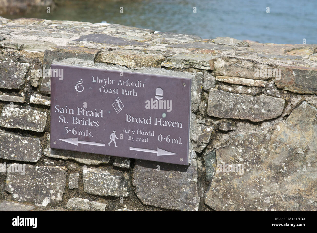 Coastal path sign mounted on a stone wall in Little Haven, Pembrokeshire, Wales, UK. - Stock Image
