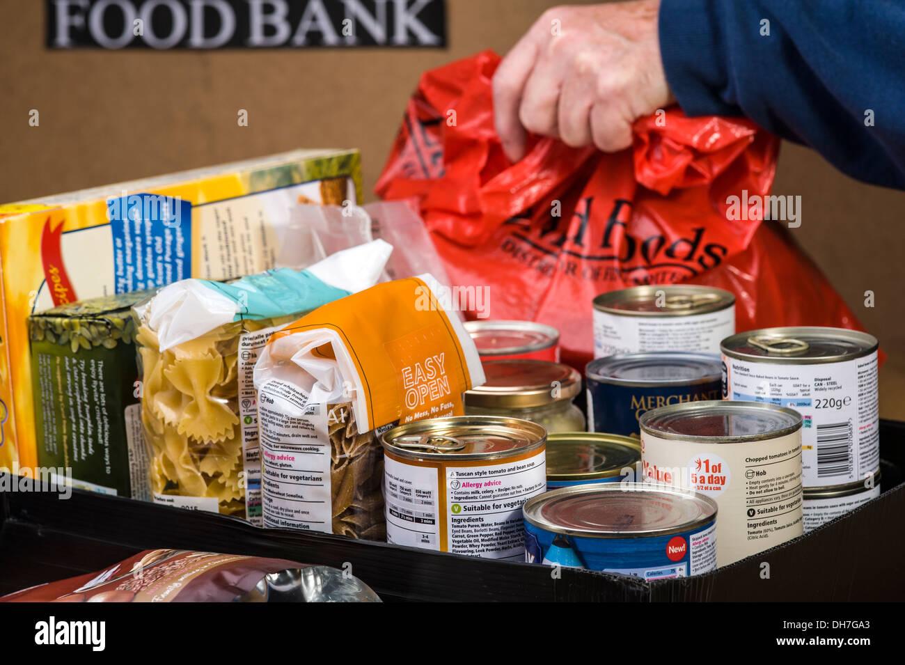 Preparing a food box at a food bank. - Stock Image