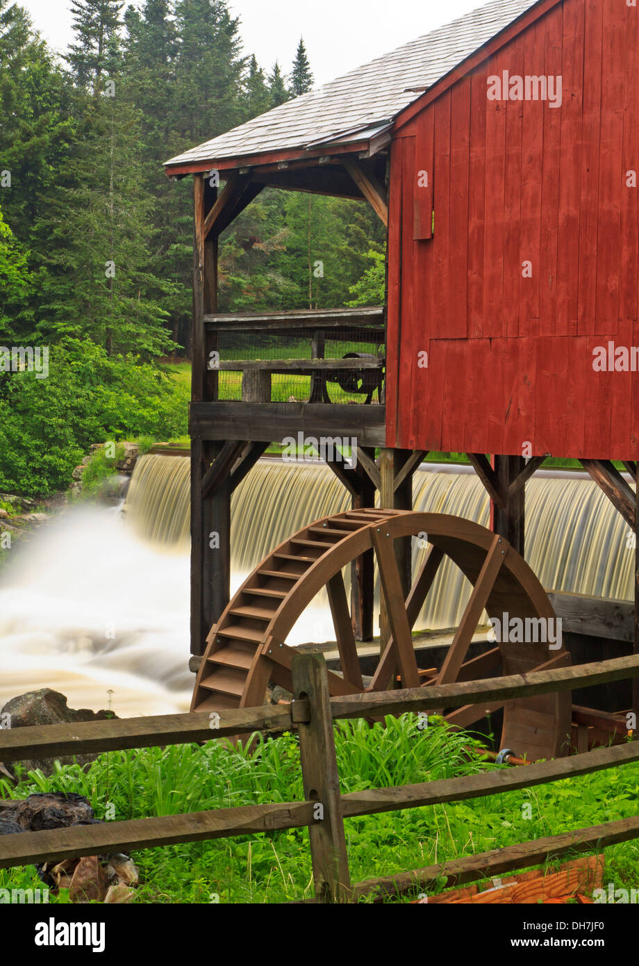 Water pours over a dam next to an old red mill with a water wheel near the Weston Playhouse in Weston, Vermont - Stock Image
