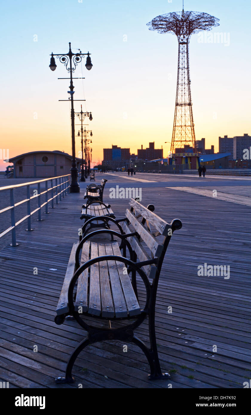 Benches on the Coney Island Boardwalk at dusk with the Parachute Drop in the background - Stock Image