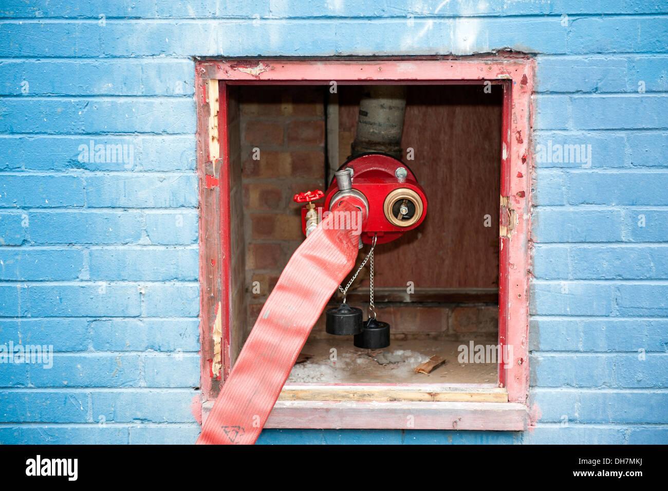 Fire hose feeding dry riser inlet valve - Stock Image