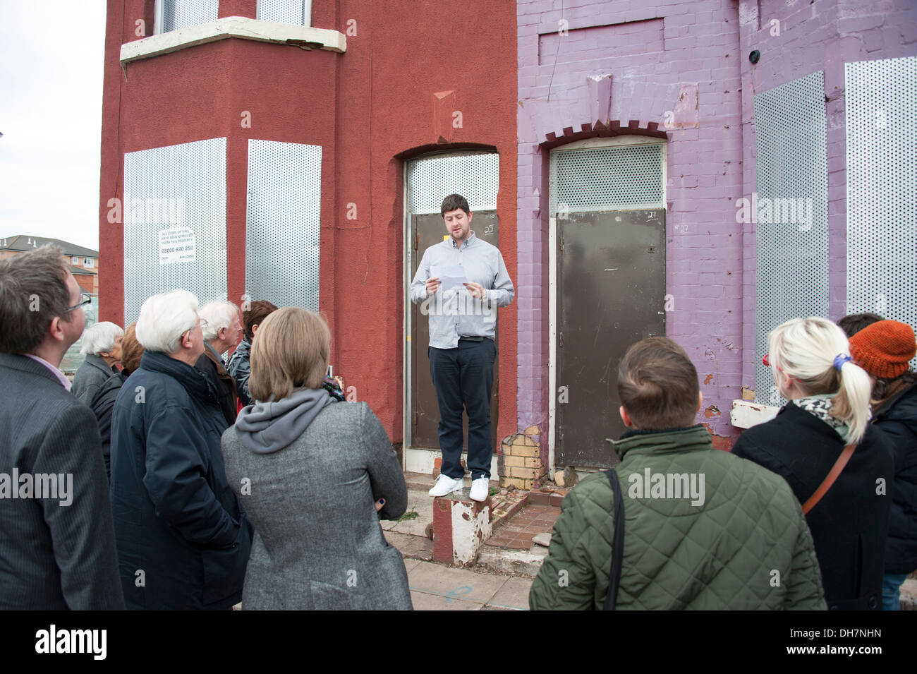 Public Speaker talking to onlookers at derelict house - Stock Image