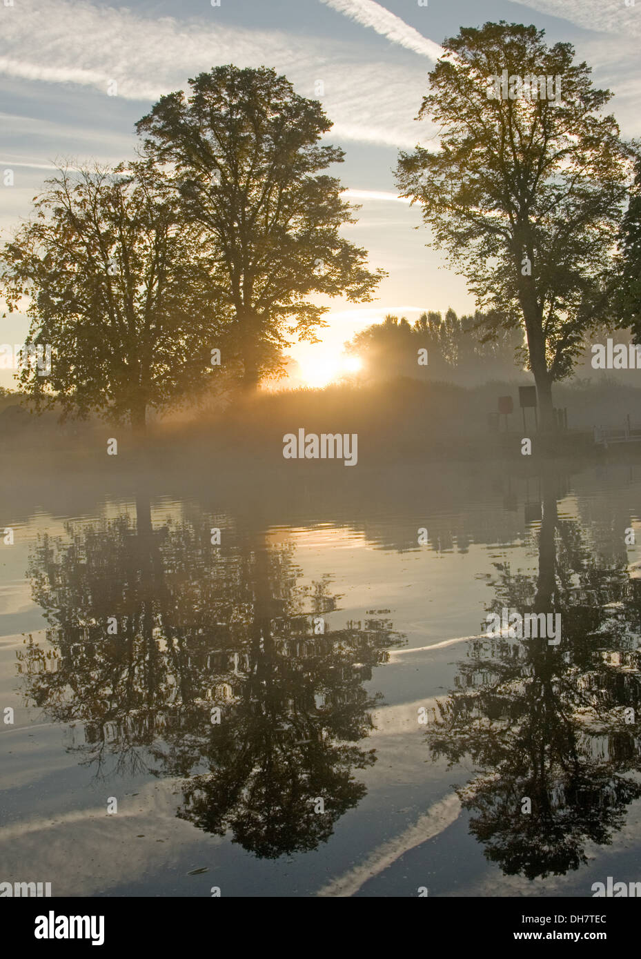 Autumnal river scene with trees reflected in the water and rising mist. - Stock Image