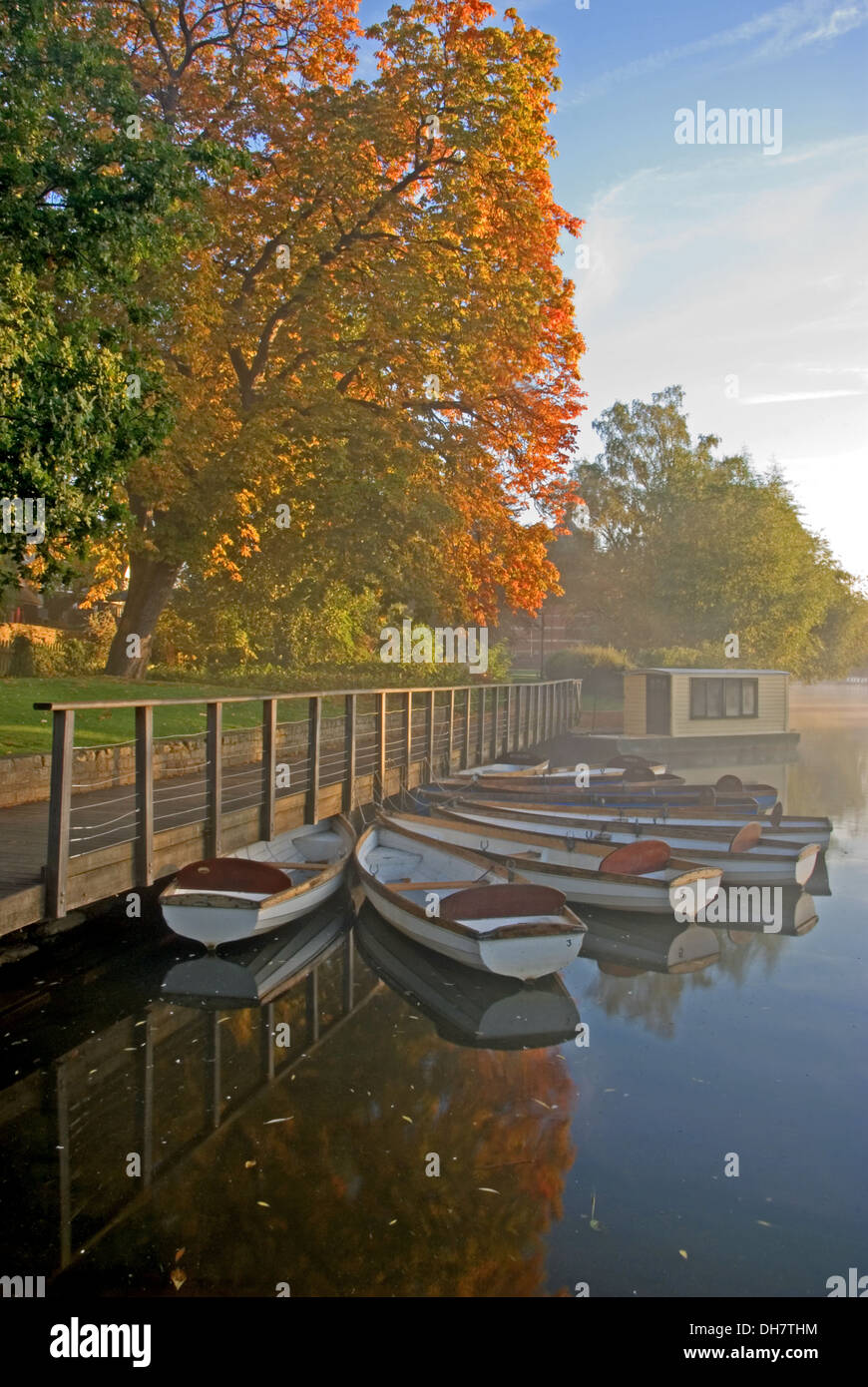 The River Avon in Stratford upon Avon with rising mists and moored rowing boats in an atmospheric autumnal river scene. - Stock Image