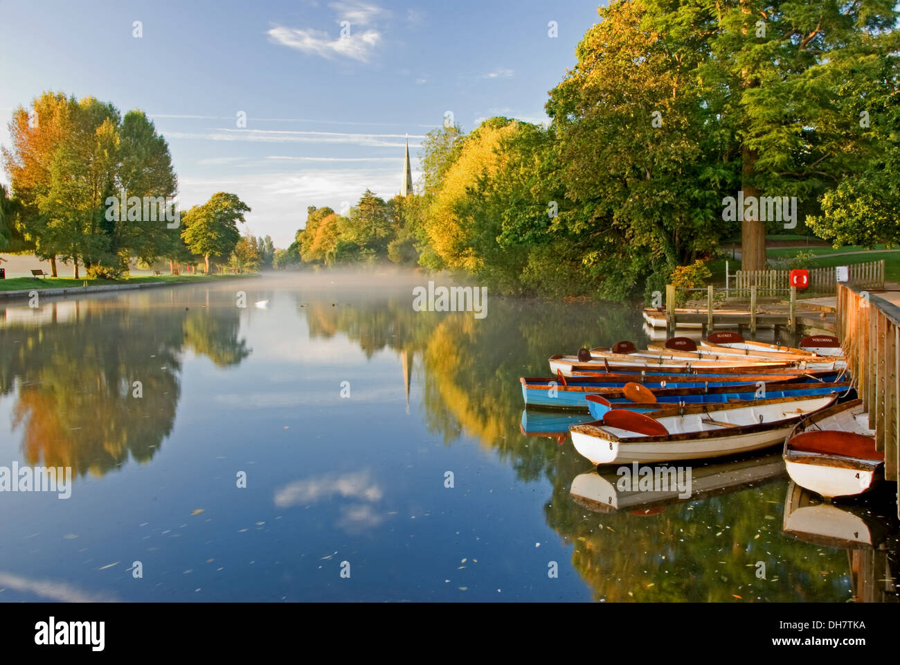 Autumnal reflections on the River Avon, with a view towards Holy Trinity church, burial place of William Shakespeare Stratford upon Avon. - Stock Image