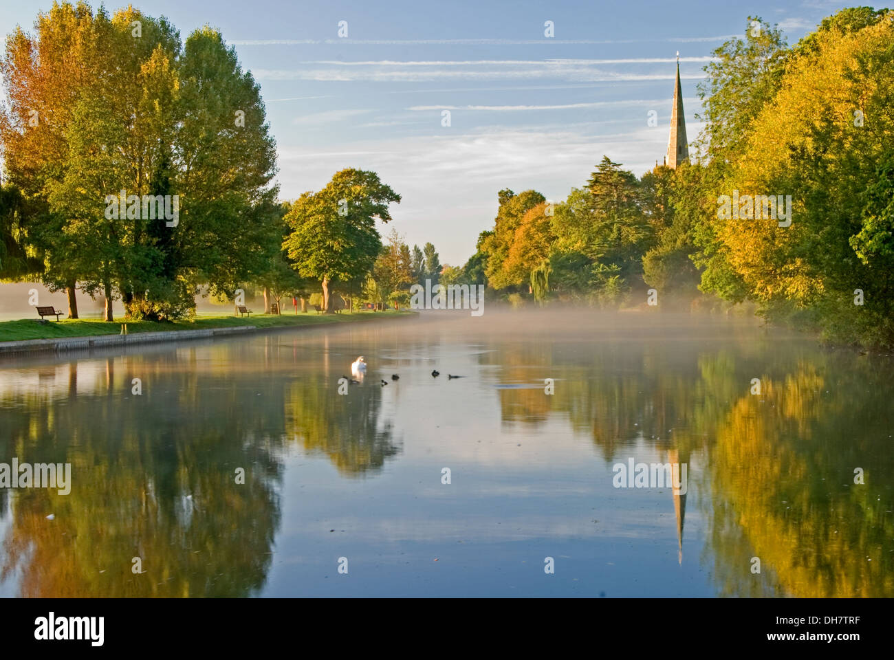 Autumnal reflections on the River Avon, with a view towards Holy Trinity church, burial place of William Shakespeare in Stratford upon Avon. - Stock Image