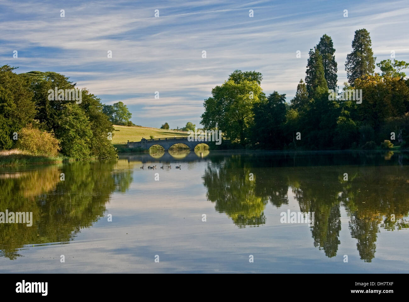 Early morning reflections in the lake at Compton Verney in South Warwickshire. - Stock Image