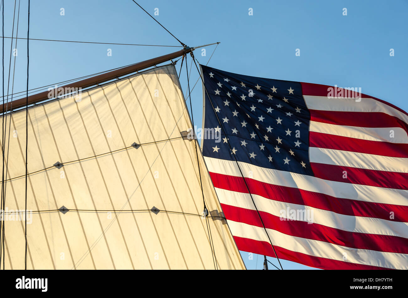 American Flag next to a sail and rigging. - Stock Image