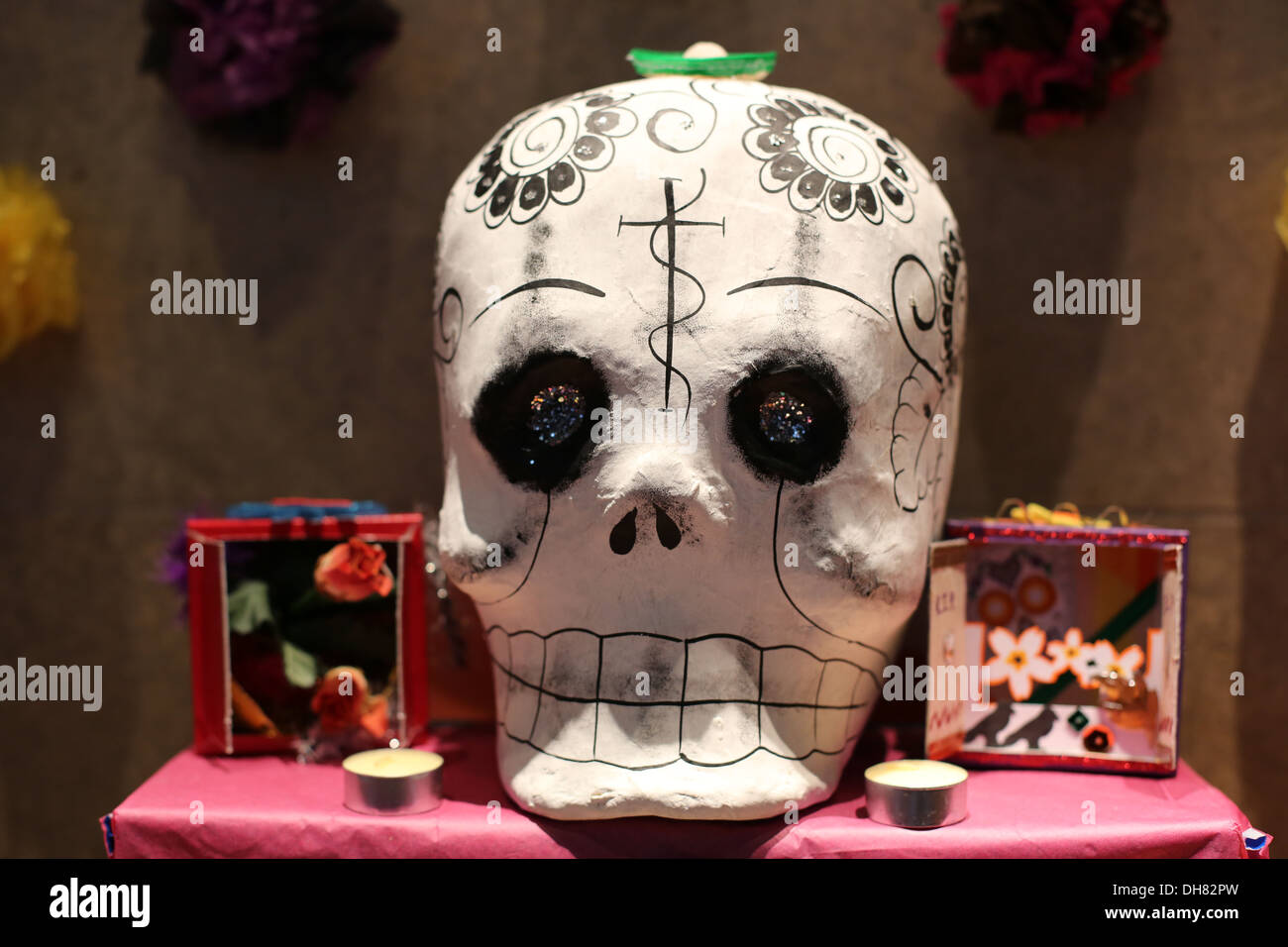 A papier mache skull and other decorations on an alter for day of the dead. - Stock Image