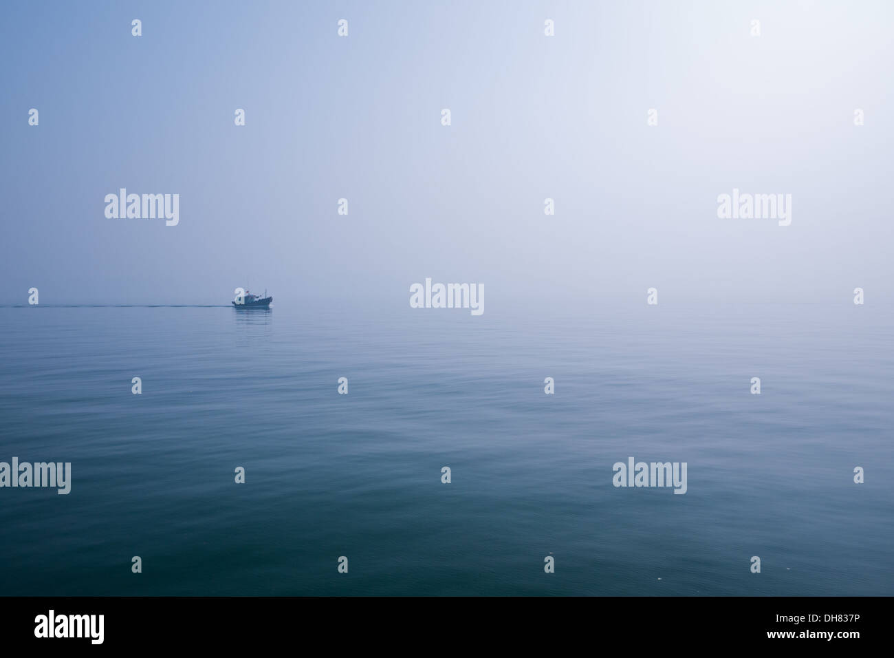 A lonely boat on Lan Ha Bay, Halong Bay, Vietnam. - Stock Image