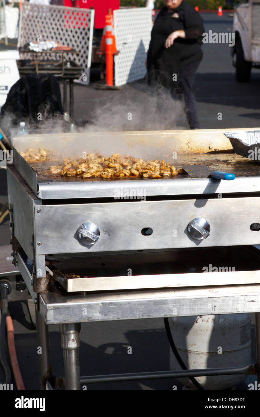 Grilled Chicken cooking outside on a gas grill at an outdoor event Stock Photo