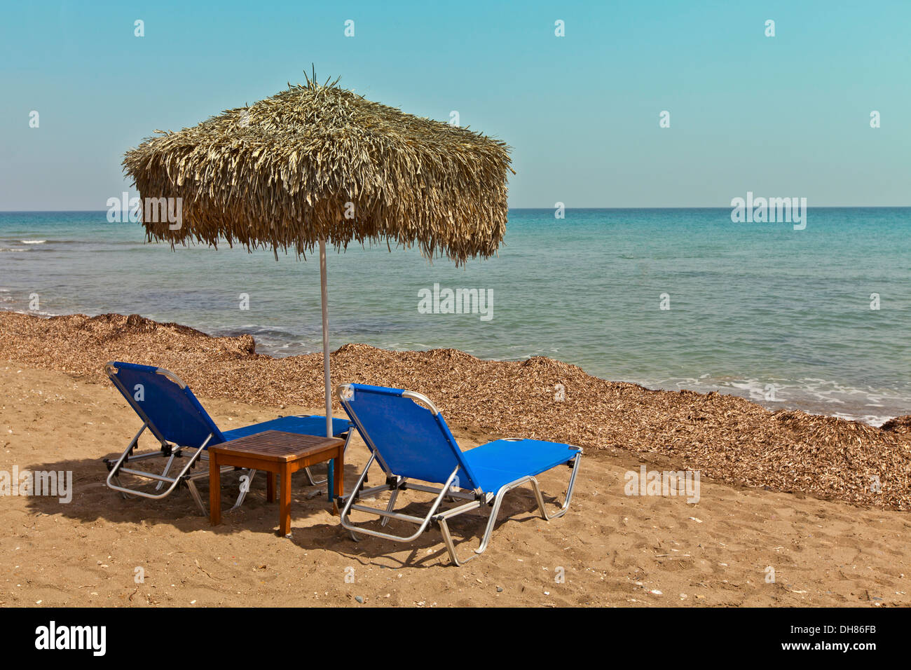 Beach scene with two sun loungers and sunshade. - Stock Image