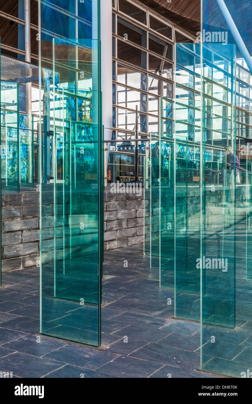 The Assembly Field outside the Senedd in Cardiff Bay Wales. Modern glass panels form a wind break, both functional and artistic. - Stock Image