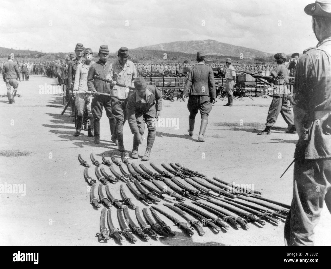 JAPANESE OFFICERS SURRENDER THEIR SWORDS TO BRITISH SOLDIERS AT THE END OF WW2 - Stock Image