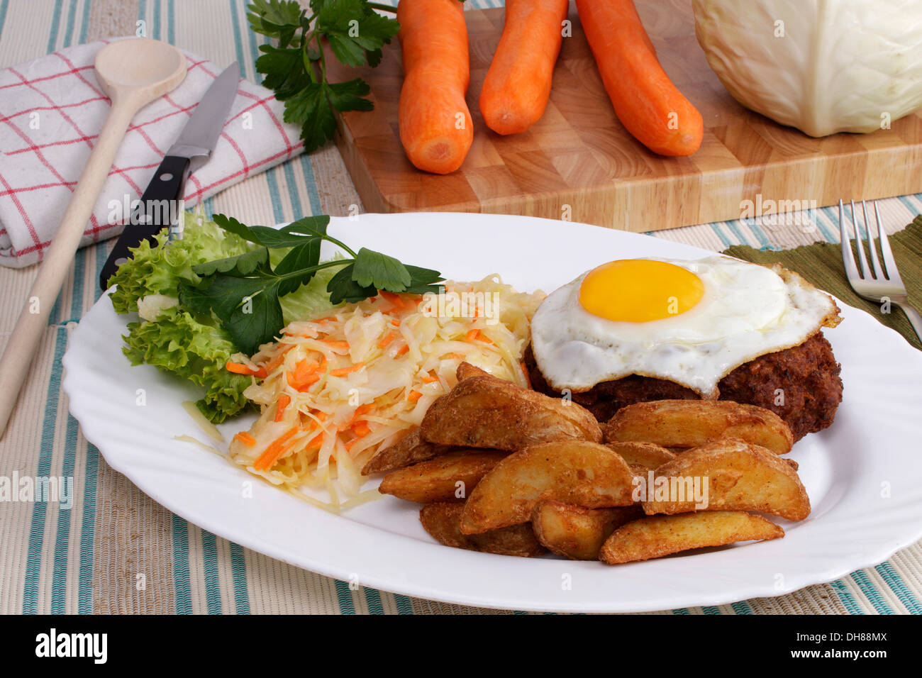 Farmers meat ball, hamburger steak, fried egg, baked potatoe wedges, coleslaw, carrots, white cabbage and flat leaf parsley on - Stock Image