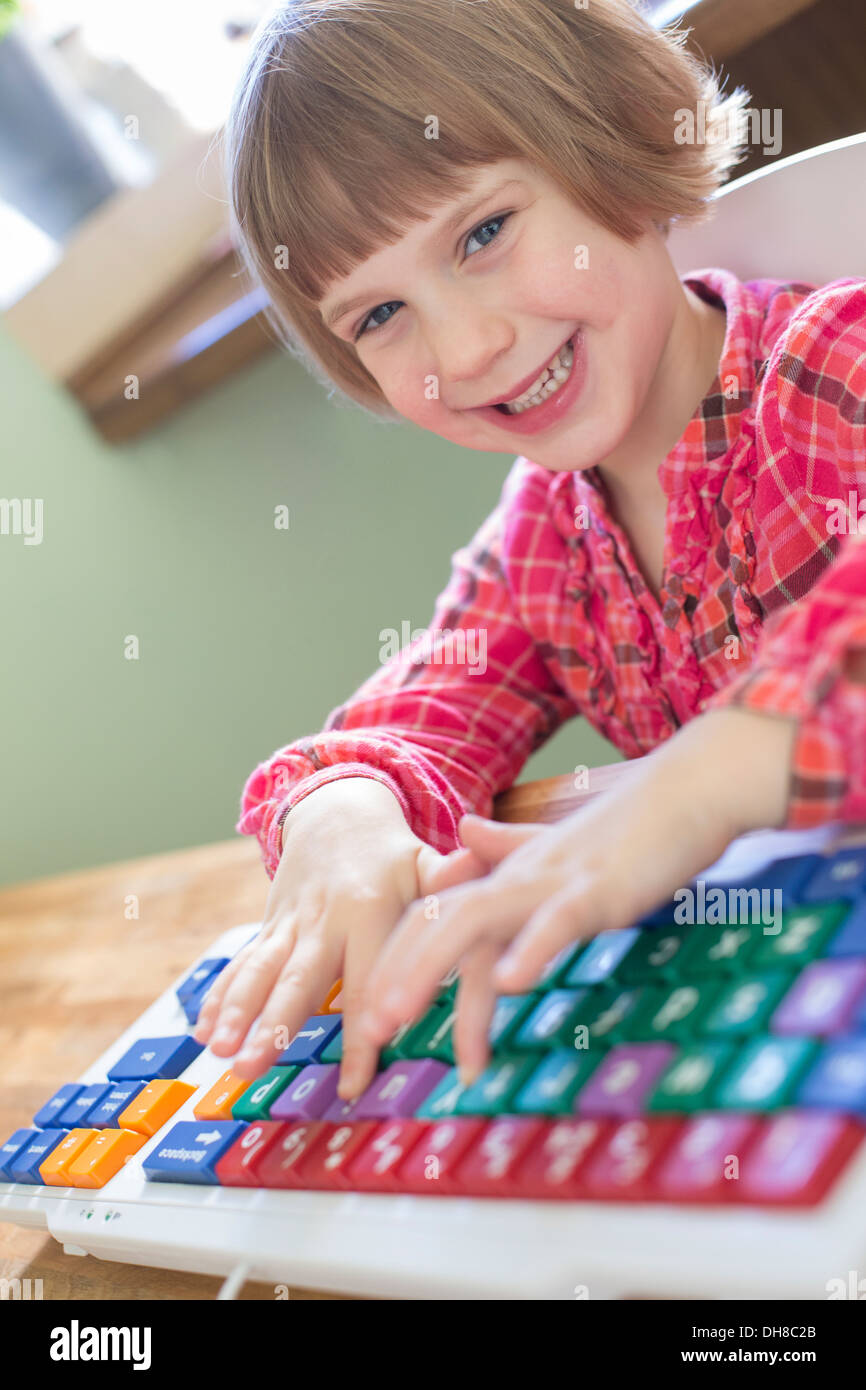 Young Girl Using Computer Keyboard At Home - Stock Image