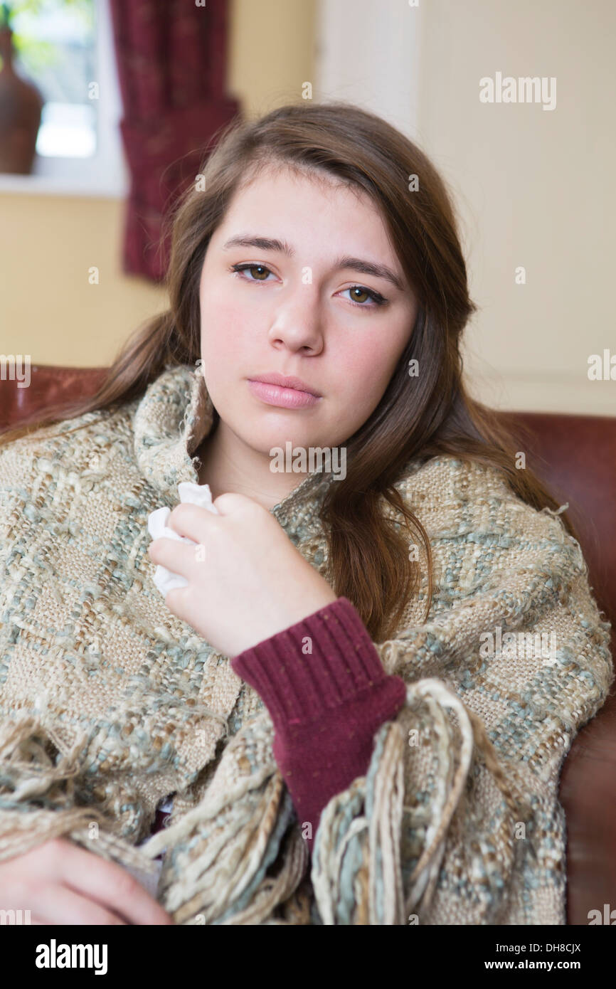 Ill Teenage Girl Sitting On Sofa Wrapped In Blanket - Stock Image