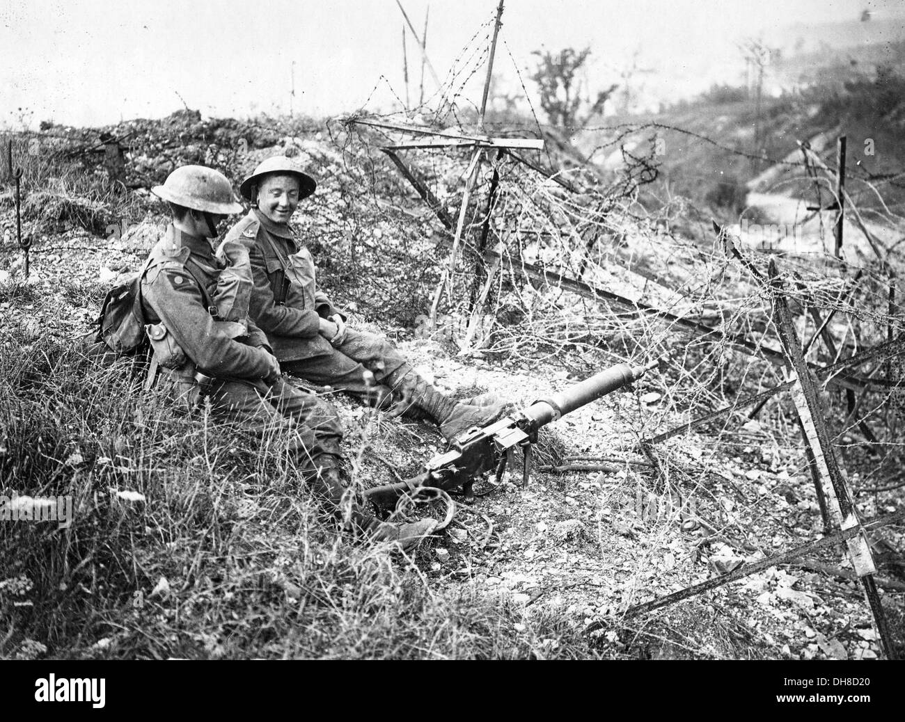 Great War trench warfare. British soldiers sit on a captured German position amongst barbed wire entanglements and discarded gun - Stock Image