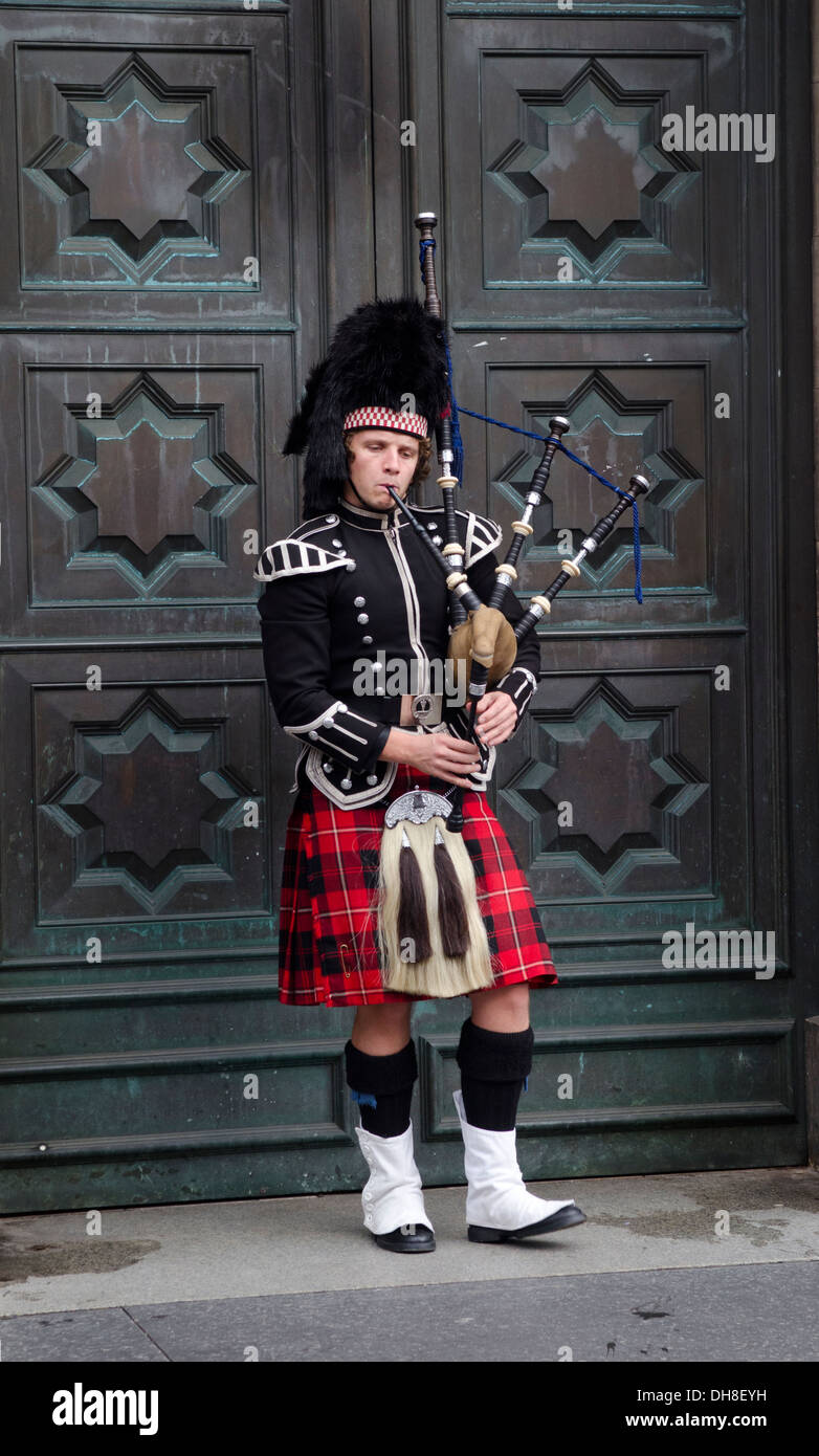 Piper in traditional costume playing bagpipes in front of grand door on the Royal Mile in Edinburgh - Stock Image