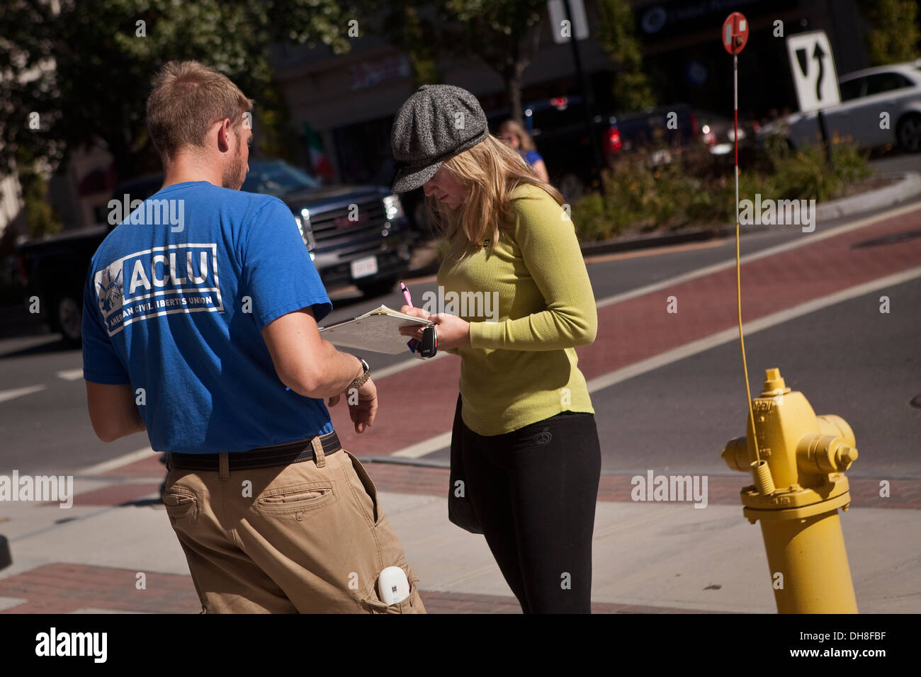 A man wearing an ACLU shirt asks a woman to sign a petition in Pittsfield, Massachusetts - Stock Image