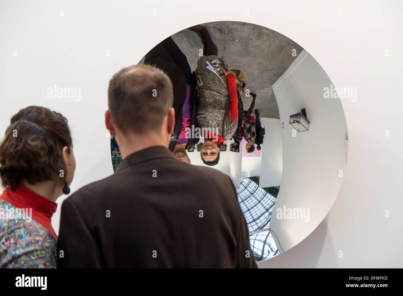 Couple looking themselves in a mirror by Anish Kapoor at the Fiac 2013 (contemporary art fair) at le Grand Palais in Paris - Stock Image
