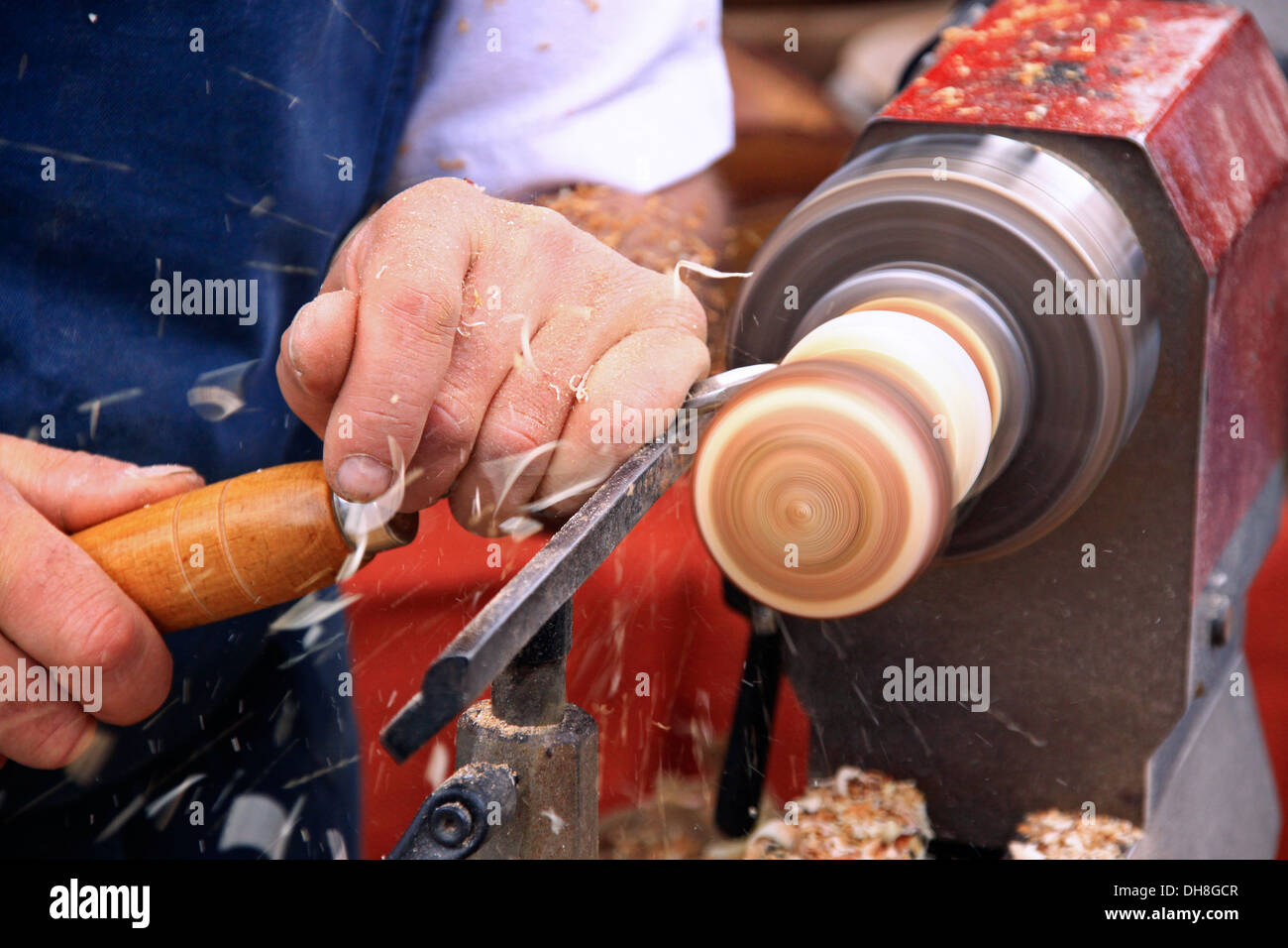 Woodworker handling gouge while working on wood with turning lathe in workshop of furniture maker Stock Photo