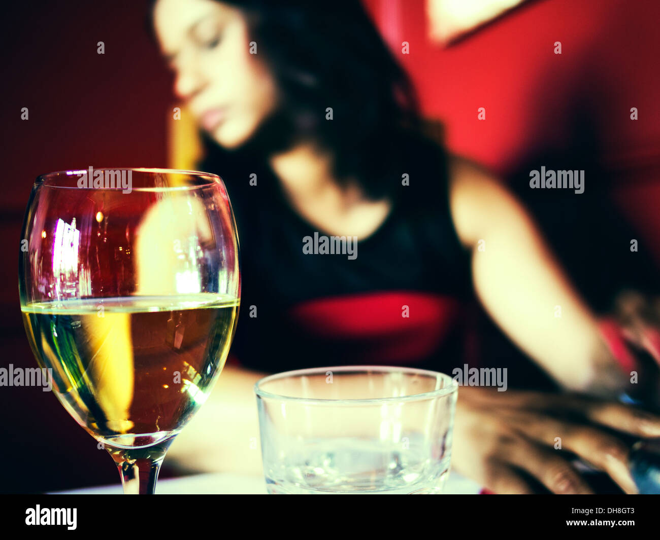Glass of wine and woman in restaurant - Stock Image