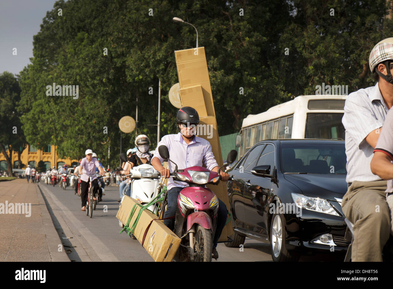 Shot of man on scooter or moped carrying various oversize packages. - Stock Image