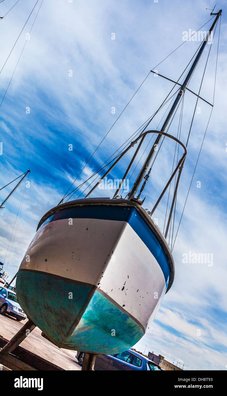 Close-up of the hull of a yacht in dry dock awaiting maintenance and repair taken on the diagonal. - Stock Image