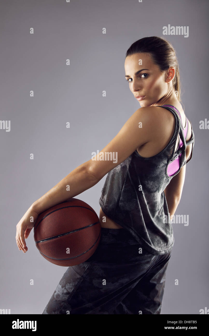 Portrait of young female basketball player looking over shoulder at camera against grey background - Stock Image