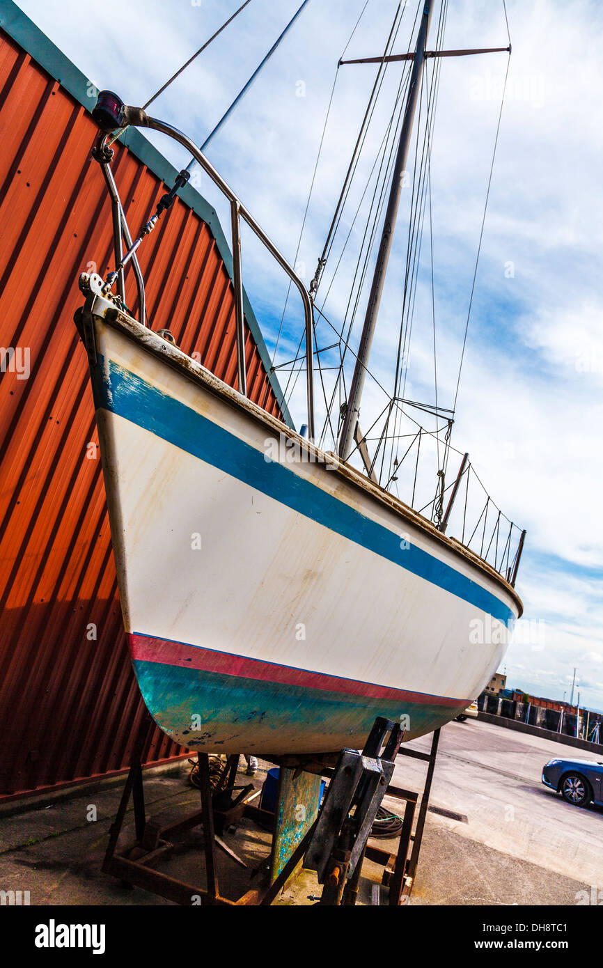 Close-up of the hull of a yacht in dry dock awaiting maintenance and repair. - Stock Image