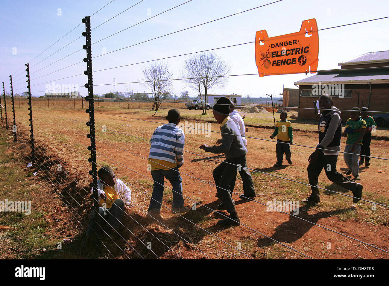 Pupils from the Thabo Vuyo school for mentally challenged children play soccer beside an electric fence at Mashoheng, South - Stock Image