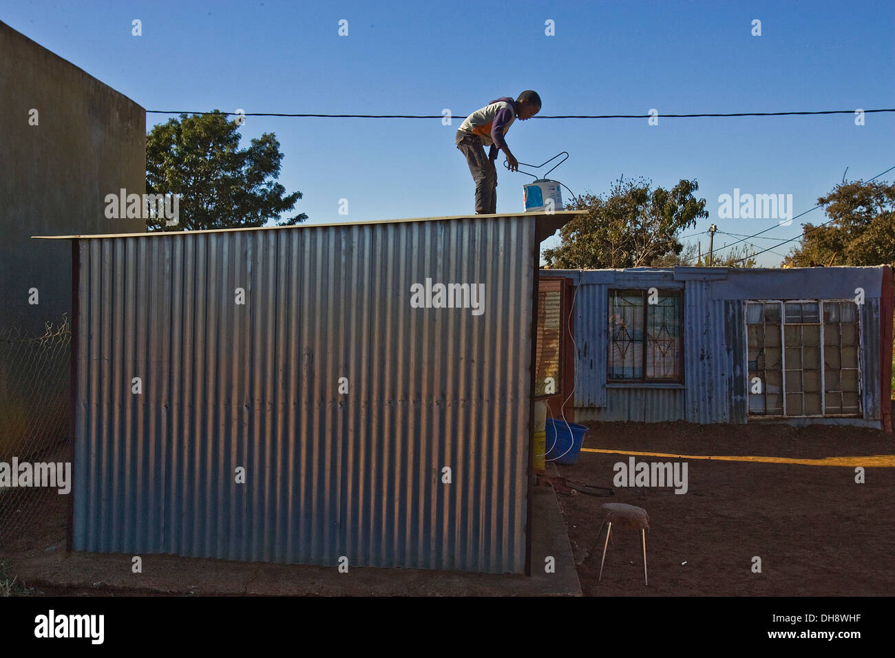 A boy in on the roof of his shack homesetting a TV antenna