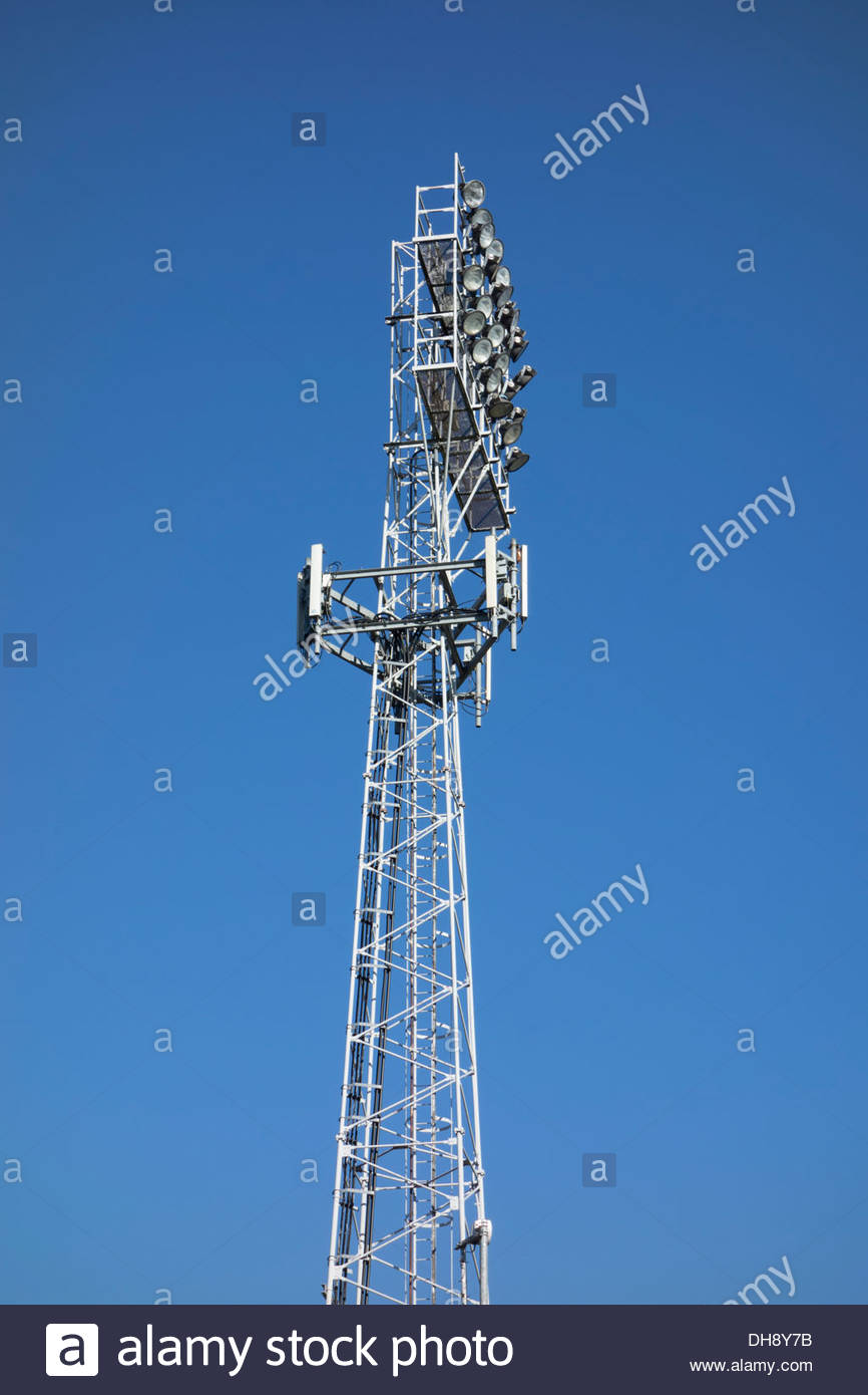 Floodlight gantry also carrying mobile phone antenna at Cambridge United Football Ground against a blue sky - Stock Image